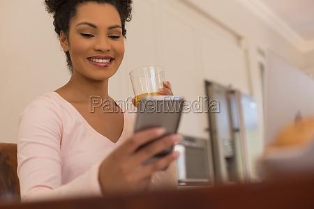 woman having orange juice while using
