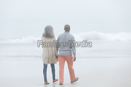couple holding hands while walking by
