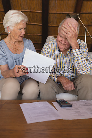 worried senior couple discussing over medical