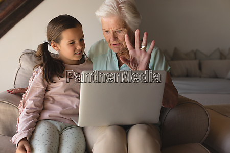 grandmother and granddaughter discussing over laptop