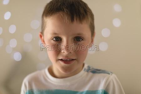 innocent boy sitting in bedroom at