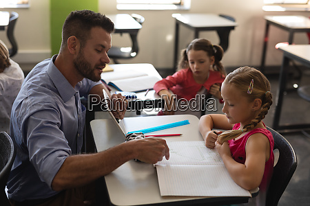young school teacher helping girl with