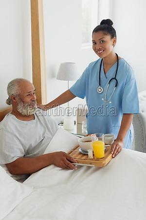 healthcare worker talking old man in