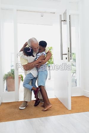 man with grandchildren by the door