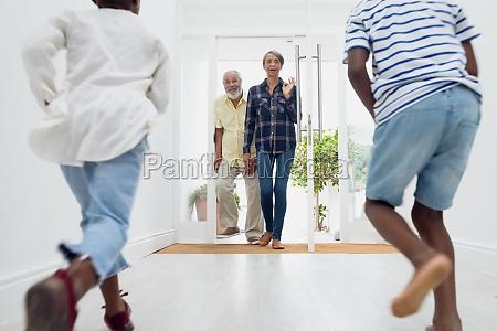 children running towards an old couple