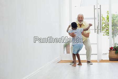 boy reaching out to hug grandmother