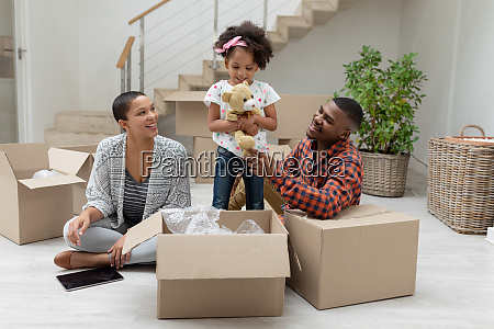 family unpacking cardboard boxes in living