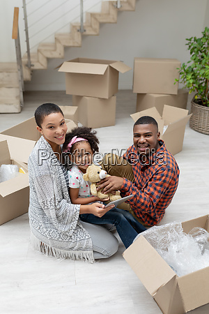 family using digital tablet while unpacking