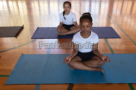 schoolkids doing yoga and meditating on