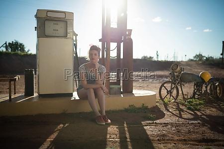 woman sitting at petrol pump station