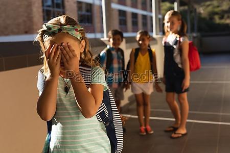 school friends bullying a crying girl