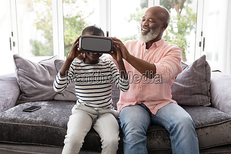 grandfather helping his grandson to wear