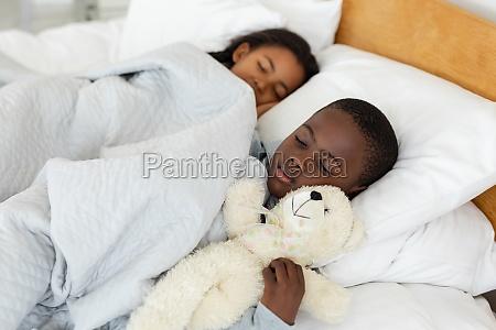 siblings sleeping together in bed in