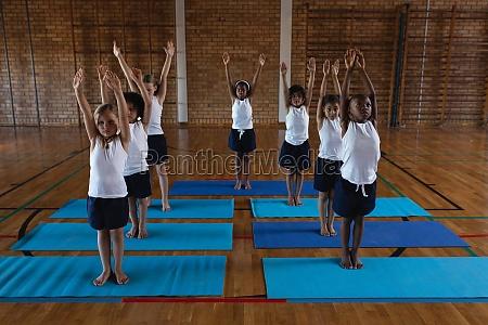 schoolkids doing yoga on a yoga