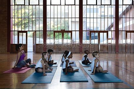 female yoga teacher and schoolkids doing