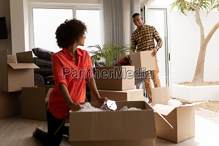 couple unpacking cardboard boxes in living