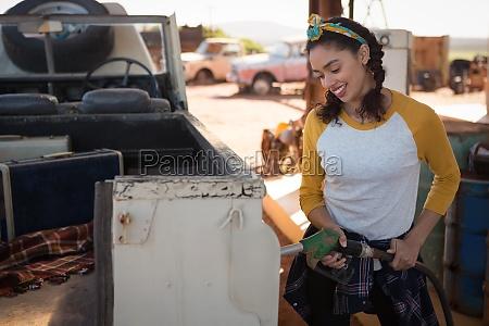 woman filling petrol in car at