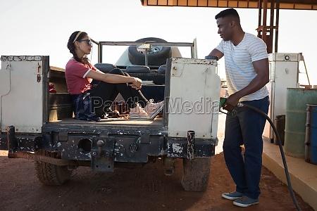 man filling petrol while woman sitting