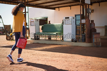 woman walking with a petrol can