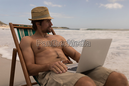 young man relaxing on sun lounger