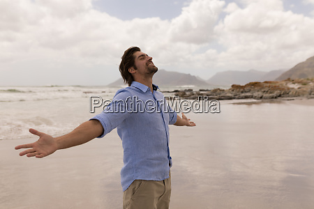 man standing with arms outstretched on