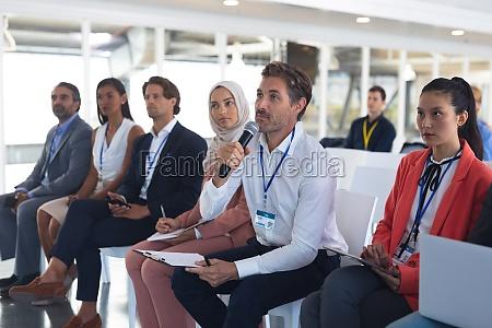 businessman asking question during seminar