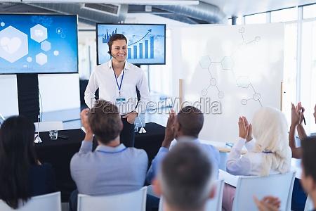 business people applauding male speaker in
