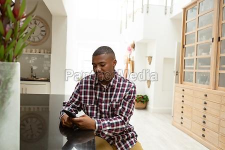 man using mobile phone on worktop