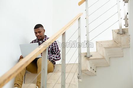 man working on laptop while sitting