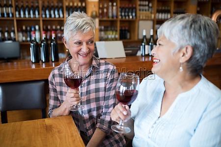 two female senior friends having red