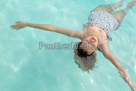 woman with eyes closed floating in