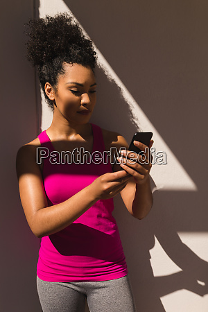 woman wearing sportswear and using mobile