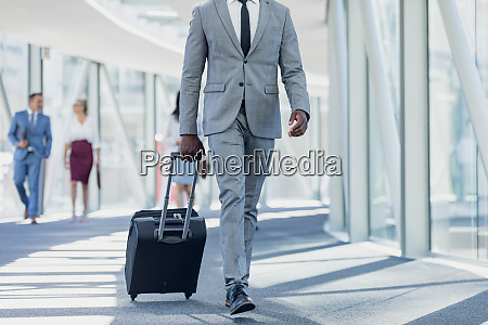 african american businessman walking in corridor