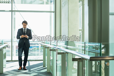 businessman using mobile phone in corridor