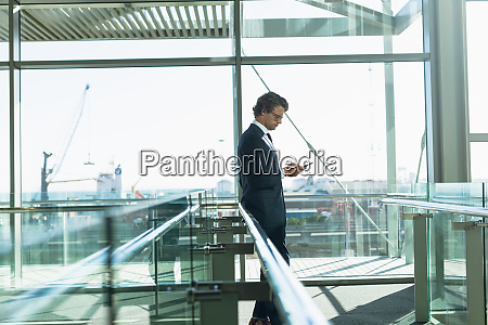 businessman leaning on railing and using