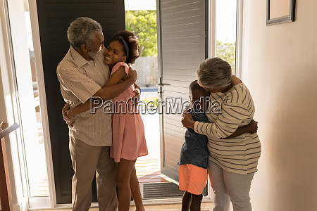 grandparents hugging their grandchildren at home