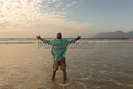 senior man standing with arms outstretched