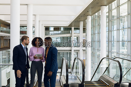 young business talking on the escalator