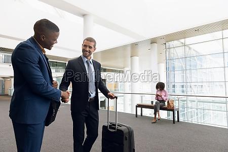 travelling businessmen shaking hands