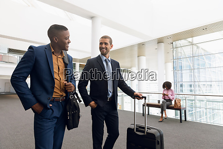 two businessmen talking while travelling with
