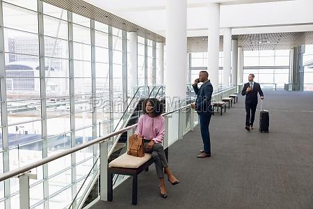 travelling business people in modern corridor