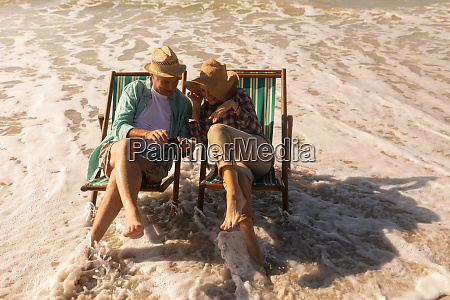 senior couple using mobile phone while