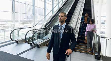 diverse business travellers leaving an escalator
