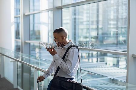 businessman using smartphone in modern building
