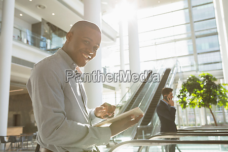 young businessman using tablet in sunlit