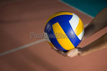 cropped hands of player with volleyball