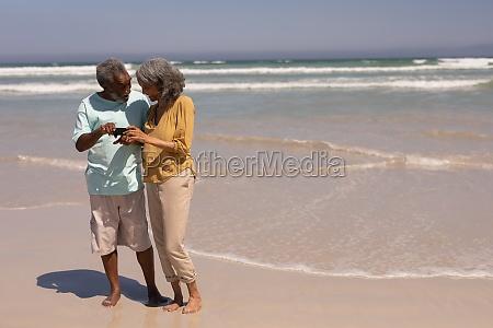 senior couple reviewing photos on mobile