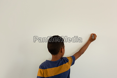 boy writing on a white wall