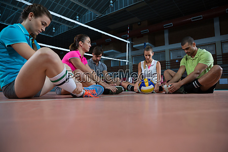 tired volleyball players sitting at court