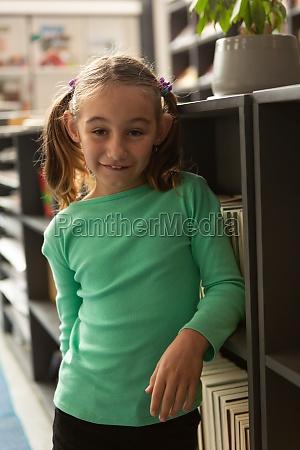 smiling schoolgirl standing in library